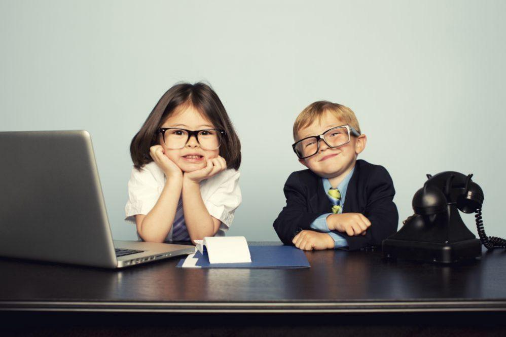 2 children, boy and girl, smiling in work attire