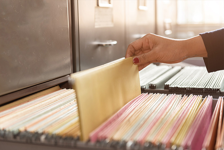 woman pulling out file folder from file cabinet